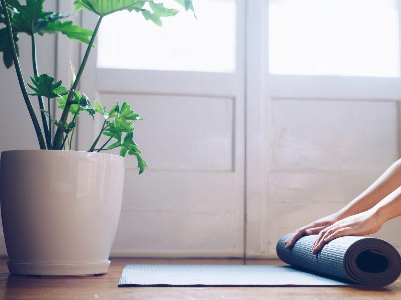 Close-up of young woman folding her  yoga mat